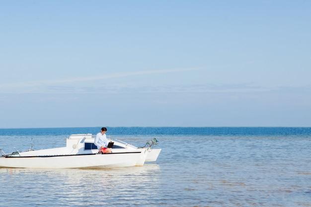 Молодой и красивый мужчина с ноутбуком на яхте.