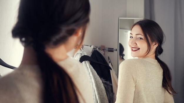 笑顔で新しいものを選ぶ洋服店の若くて幸せなブルネットの女性。ブティック