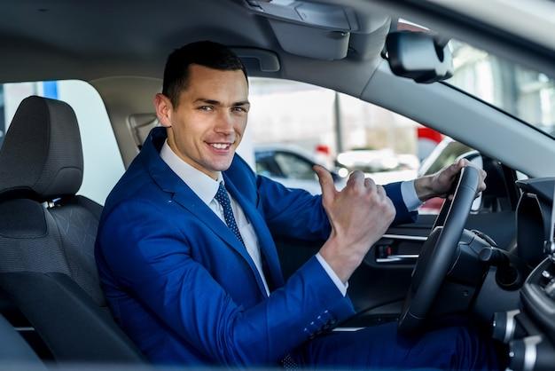 쇼룸에서 새 차에 앉아 젊고 행복 한 사업가