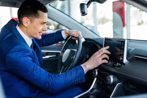 Молодой и счастливый бизнесмен, сидя в новой машине в автосалоне
