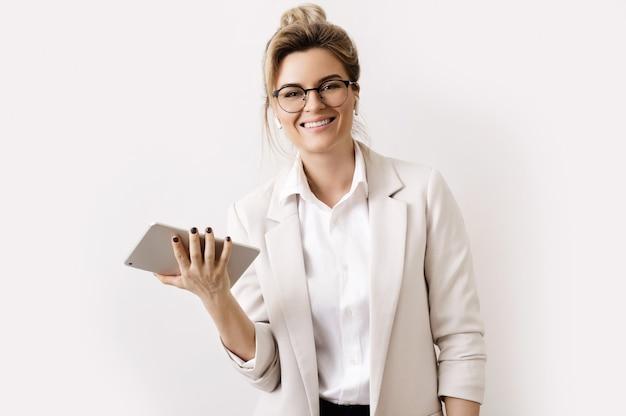 Молодая и счастливая бизнесвумен с планшетным пк на сером