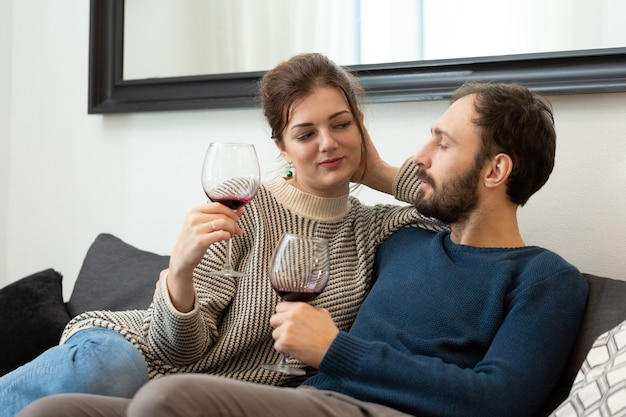 Молодая и счастливая пара пьет вино и отдыхает дома