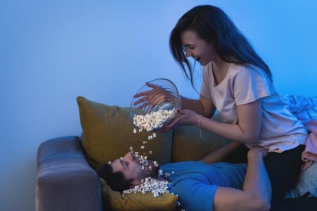 Молодая и счастливая пара ест попкорн и смотрит фильм дома