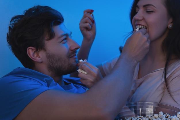 Молодая и счастливая пара ест попкорн и смотрит фильм
