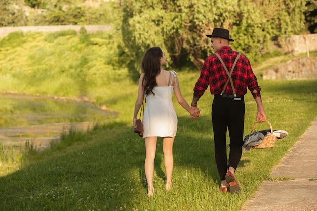 夏の日のパークサイドに広がるピクニックを楽しむ若い、幸せなカップル