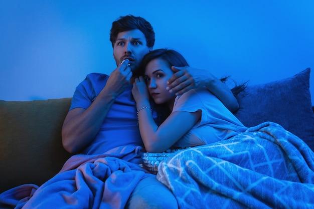 Молодая и счастливая пара смотрит фильм ужасов дома