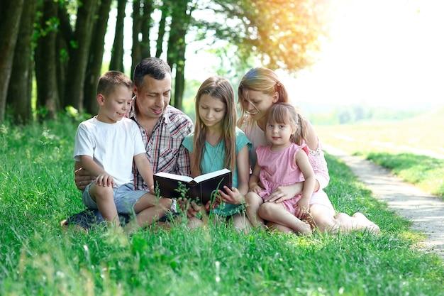 Молодая и счастливая семья с детьми, читающими библию на природе