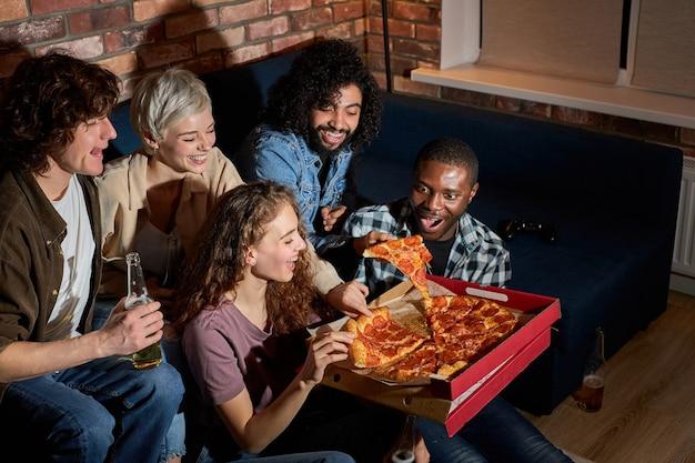 Молодые и счастливые друзья едят пиццу и смотрят дома фильм или сериал, американские студенты в свободное время после уроков отдыхают после тяжелой недели.