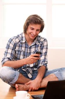 Молодой и счастливый парень, с помощью мобильного телефона