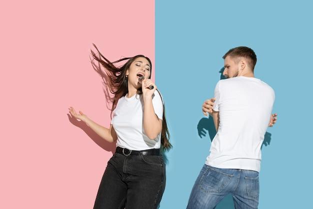 Молодой и счастливый мужчина и женщина в повседневной одежде на розовой, синей двухцветной стене, поют и танцуют
