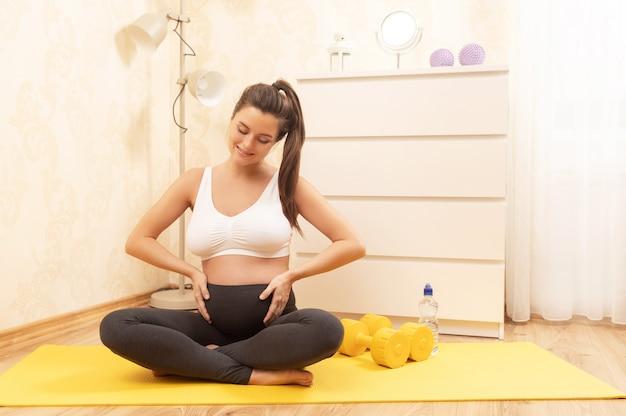 Молодая и счастливая беременная женщина во время фитнес-тренировки дома