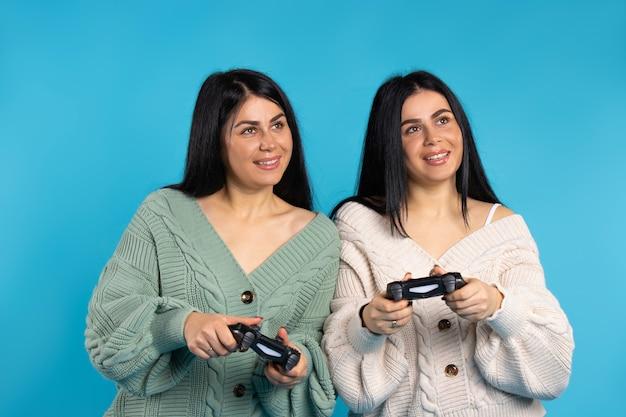 조이스틱을 들고 젊고 행복한 쌍둥이 자매는 집에서 재미를