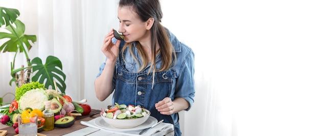 デニムの服で明るい背景に、テーブルでサラダを食べる若い、幸せな女。健康的な自家製食品のコンセプト。