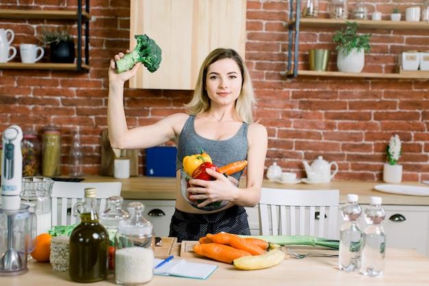 モダンなキッチンで健康食品のテーブルの上に立っている間、左手に新鮮な野菜と右手にブロッコリーのガラスのボウルを保持している若くて幸せな女。健康食品のコンセプト