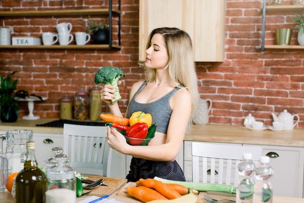 Молодая и счастливая женщина держа стеклянный шар с свежими овощами в левой руке и брокколи в правой руке пока стоящ на таблице с здоровой едой в современной кухне. концепция здорового питания