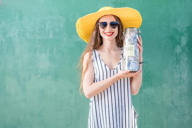 緑の背景で旅行するためのお金でいっぱいの瓶を保持している黄色い帽子の若くて幸せな女性。夏休みのコンセプトのためのお金の節約