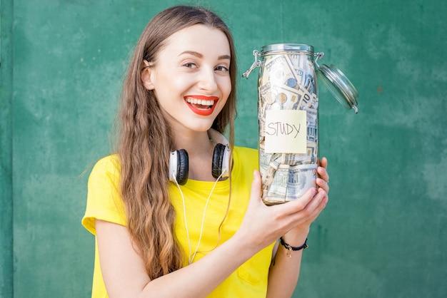 노란색 티셔츠를 입은 젊고 행복한 여성이 연구를 위해 저축한 병을 들고 있다