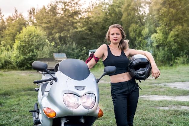 Молодая и счастливая женщина на мотоцикле позирует на открытом воздухе