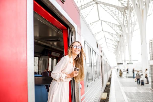 Молодая и счастливая женщина вытаскивает лицо из двери поезда в поисках кого-то на вокзале