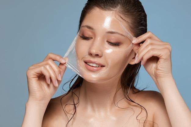 Молодая и счастливая женщина снимает маску с лица и смотрит в сторону