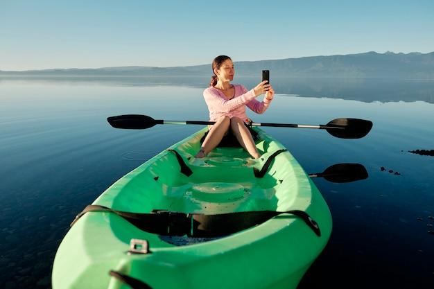 진정 푸른 호수 한가운데 그녀의 휴대 전화로 비디오를 만드는 카약에 앉아 젊고 행복한 여자.