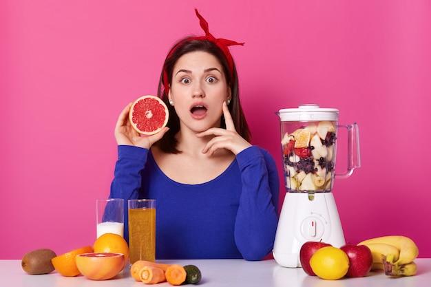 若くて健康な女性は驚くべき表情をしていて、ピンクに分離されたグレープフルーツの部分を手に持っています。テーブルの表面に新鮮な果物や野菜がたくさん。