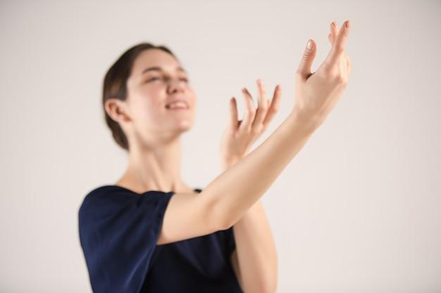 젊고 믿을 수 없을만큼 아름다운 발레리나는 스튜디오에서 춤을 추고 있습니다.