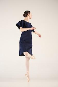 若い、信じられないほど美しいバレリーナが青いスタジオで踊っています