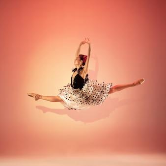 Молодая и невероятно красивая балерина позирует и танцует в красной студии, залитой светом.
