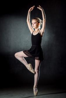 スタジオでポーズをとって踊る、若くて信じられないほど美しいバレリーナ。バレエダンサー。