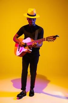 젊고 즐거운 아프리카계 미국인 음악가가 기타를 연주하고 네온 불빛 아래 그라데이션 오렌지색 스튜디오 배경에서 노래합니다. 음악, 취미, 축제의 개념. 현대 예술가의 다채로운 초상화입니다.