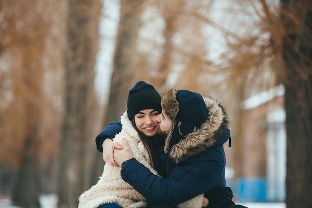 Молодая и прекрасная пара обнимается в зимнем парке
