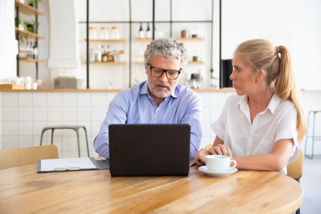 Молодые и зрелые коллеги по бизнесу встречаются в коворкинге, сидят за открытым ноутбуком, обсуждают контент