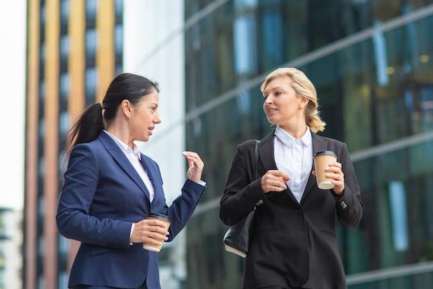 屋外で一緒に歩く、話している、プロジェクトについて話し合っている、またはチャットしているテイクアウトのコーヒーカップを持つ若いおよび中年の女性同僚。ミディアムショット。休憩コンセプト