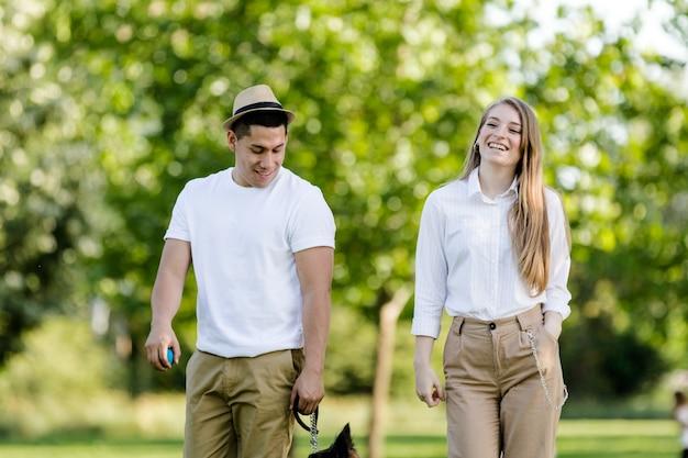 公園で犬のボーダーコリーと歩いたり遊んだりする若くて現代的なカップル