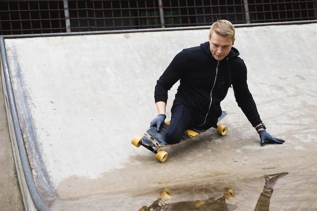 스케이트 파크에서 롱 보드를 들고 젊고 의욕적 인 장애인 남자