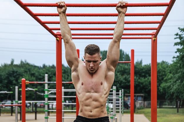 鉄棒で懸垂をしている若くて筋肉質の男