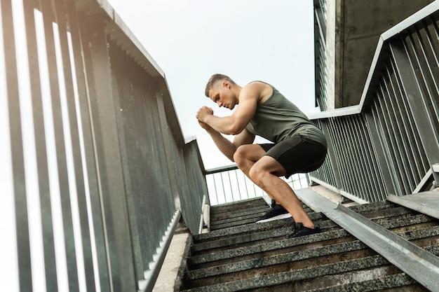 Staircase에 운동하는 동안 젊고 근육 질의 남자