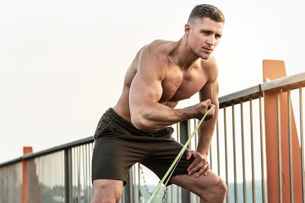 거리에 저항 고무 밴드와 함께 운동하는 동안 젊고 근육질의 남자. 이두근 컬 운동.