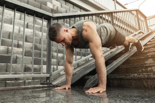 젊고 근육질의 남자가 거리에서 교정 운동을하는 동안 팔 굽혀 펴기를하고 있습니다.