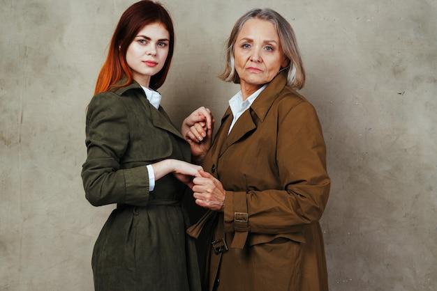 老婆と老婆がコートのポーズで隣同士に立っています。高品質の写真