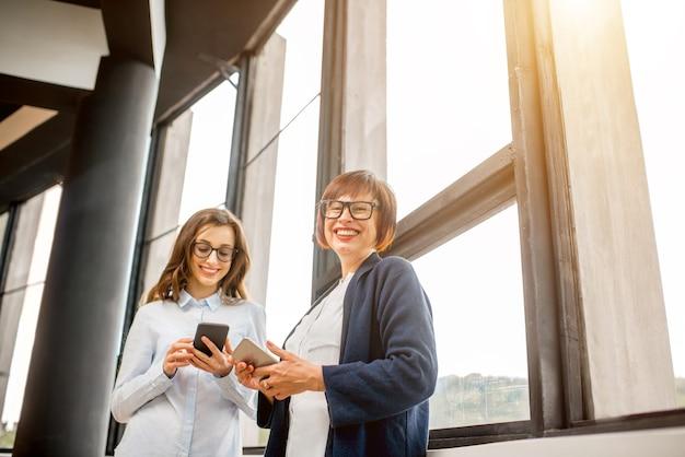 Молодые и пожилые женщины-предприниматели, стоящие у окна в офисе