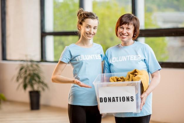 Молодые и пожилые добровольцы, одетые в синие футболки, держат контейнер с пожертвованной одеждой в помещении в офисе
