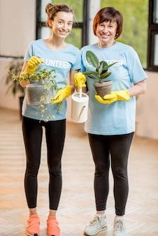 실내에서 녹색 식물을 돌보는 파란색 티셔츠를 입은 젊은이와 노인 자원 봉사자