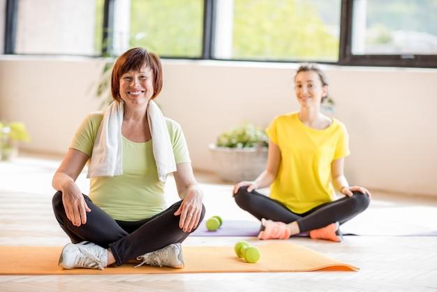 屋内でのヨガトレーニング中に座っているスポーツウェアの若い年配の女性