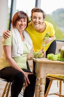 ダンベルで運動し、窓の背景に屋内で健康的な食べ物を食べる若い女性と年配の女性