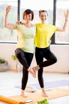 スポーツウェアの若い女性と年配の女性は、自宅やジムで一緒にヨガをしています。