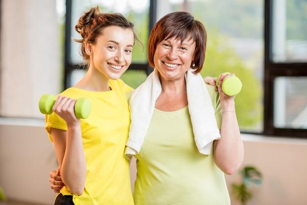 窓の背景に屋内でダンベルを使ってスポーツウェアのトレーニングをしている若い女性と年配の女性