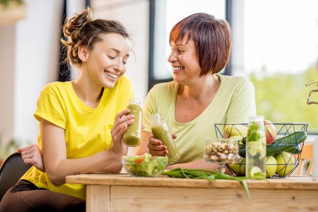 窓の背景に屋内でスポーツトレーニングをした後、健康的な食べ物や新鮮な飲み物と一緒に座っている若い女性と年配の女性