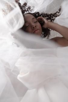 若くてかなり黒い女の子が朝白いカーテンでポーズ